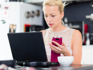 Woman holding phone in front of laptop